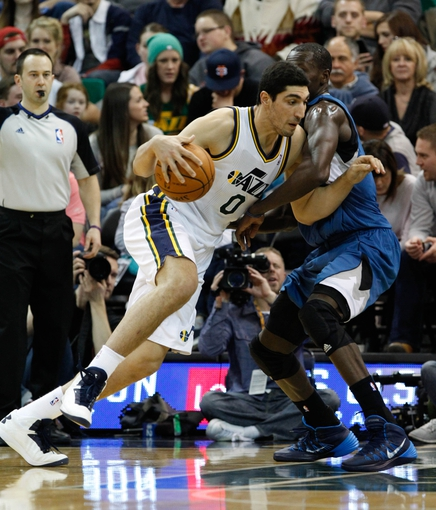 Feb 22, 2014; Salt Lake City, UT, USA; Utah Jazz center Enes Kanter (0) moves past Minnesota Timberwolves center Gorgui Dieng (5) during the second quarter at EnergySolutions Arena. Mandatory Credit: Chris Nicoll-USA TODAY Sports