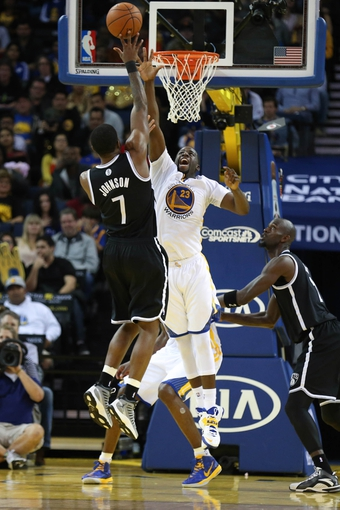 Feb 22, 2014; Oakland, CA, USA; Brooklyn Nets shooting guard Joe Johnson (7) shoots the ball against Golden State Warriors small forward Draymond Green (23) during the fourth quarter at Oracle Arena. The Golden State Warriors defeated the Brooklyn Nets 93-86. Mandatory Credit: Kelley L Cox-USA TODAY Sports