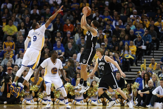 Feb 22, 2014; Oakland, CA, USA; Brooklyn Nets point guard Deron Williams (8) shoots the ball against Golden State Warriors small forward Andre Iguodala (9) during the fourth quarter at Oracle Arena. The Golden State Warriors defeated the Brooklyn Nets 93-86. Mandatory Credit: Kelley L Cox-USA TODAY Sports