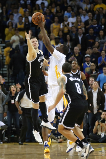 Feb 22, 2014; Oakland, CA, USA; Golden State Warriors small forward Draymond Green (23) controls the ball against Brooklyn Nets power forward Mirza Teletovic (33) during the fourth quarter at Oracle Arena. The Golden State Warriors defeated the Brooklyn Nets 93-86. Mandatory Credit: Kelley L Cox-USA TODAY Sports