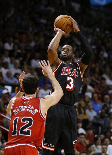 Feb 23, 2014; Miami, FL, USA; Miami Heat shooting guard Dwyane Wade (3) shoots the ball over Chicago Bulls shooting guard Kirk Hinrich (12) in the second half at American Airlines Arena. The Heat won 93-79.  Mandatory Credit: Robert Mayer-USA TODAY Sports
