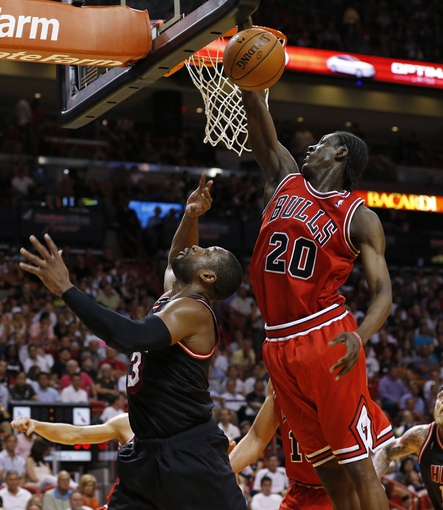 Feb 23, 2014; Miami, FL, USA; Chicago Bulls shooting guard Tony Snell (20) blocks a shot by Miami Heat shooting guard Dwyane Wade (3) in the second half at American Airlines Arena.The Heat won 93-79.  Mandatory Credit: Robert Mayer-USA TODAY Sports