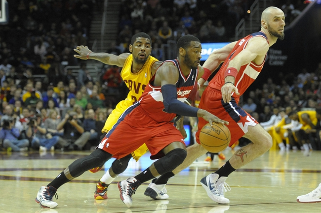 Feb 23, 2014; Cleveland, OH, USA; Washington Wizards point guard John Wall (2) dribbles around center Marcin Gortat (4) and Cleveland Cavaliers point guard Kyrie Irving (2) in the second quarter at Quicken Loans Arena. Mandatory Credit: David Richard-USA TODAY Sports
