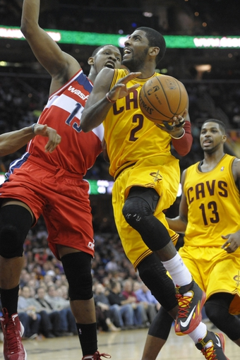 Feb 23, 2014; Cleveland, OH, USA; Cleveland Cavaliers point guard Kyrie Irving (2) drives against Washington Wizards center Kevin Seraphin (13) in the fourth quarter at Quicken Loans Arena. Mandatory Credit: David Richard-USA TODAY Sports