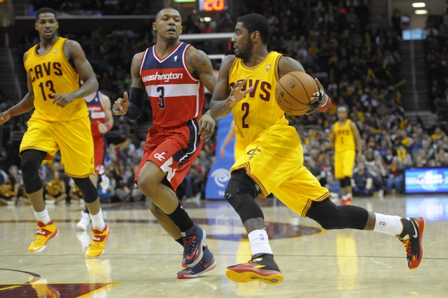 Feb 23, 2014; Cleveland, OH, USA; Cleveland Cavaliers point guard Kyrie Irving (2) drives against Washington Wizards shooting guard Bradley Beal (3) in the fourth quarter at Quicken Loans Arena. Mandatory Credit: David Richard-USA TODAY Sports