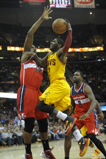 Feb 23, 2014; Cleveland, OH, USA; Cleveland Cavaliers point guard Kyrie Irving (2) drives between Washington Wizards center Kevin Seraphin (13) and small forward Martell Webster (9) in the third quarter at Quicken Loans Arena. Mandatory Credit: David Richard-USA TODAY Sports