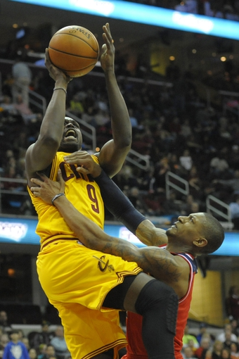Feb 23, 2014; Cleveland, OH, USA; Cleveland Cavaliers small forward Luol Deng (9) shoots against Washington Wizards shooting guard Bradley Beal (3) in the third quarter at Quicken Loans Arena. Mandatory Credit: David Richard-USA TODAY Sports