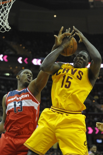 Feb 23, 2014; Cleveland, OH, USA; Washington Wizards center Kevin Seraphin (13) and Cleveland Cavaliers small forward Anthony Bennett (15) reach for a rebound in the third quarter at Quicken Loans Arena. Mandatory Credit: David Richard-USA TODAY Sports