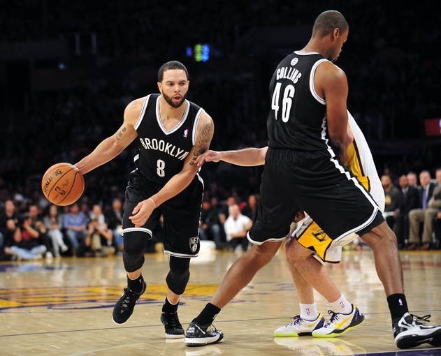 February 23, 2014; Los Angeles, CA, USA; Brooklyn Nets point guard Deron Williams (8) moves the ball as center Jason Collins (46) provides a screen against the Los Angeles Lakers during the first half at Staples Center. Mandatory Credit: Gary A. Vasquez-USA TODAY Sports