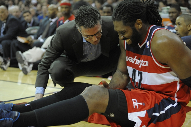 Feb 23, 2014; Cleveland, OH, USA; Washington Wizards power forward Nene Hilario (42) reacts on the court after a knee injury in the third quarter against the Cleveland Cavaliers at Quicken Loans Arena. Mandatory Credit: David Richard-USA TODAY Sports