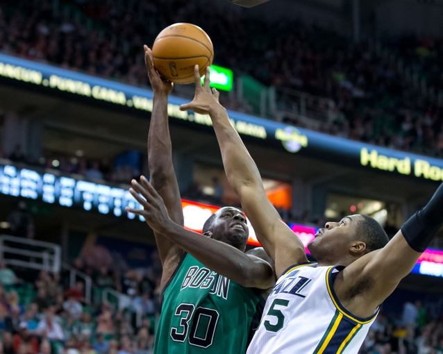 Feb 24, 2014; Salt Lake City, UT, USA; Utah Jazz center Derrick Favors (15) blocks the shot of Boston Celtics power forward Brandon Bass (30) during the first half at EnergySolutions Arena. Mandatory Credit: Russ Isabella-USA TODAY Sports