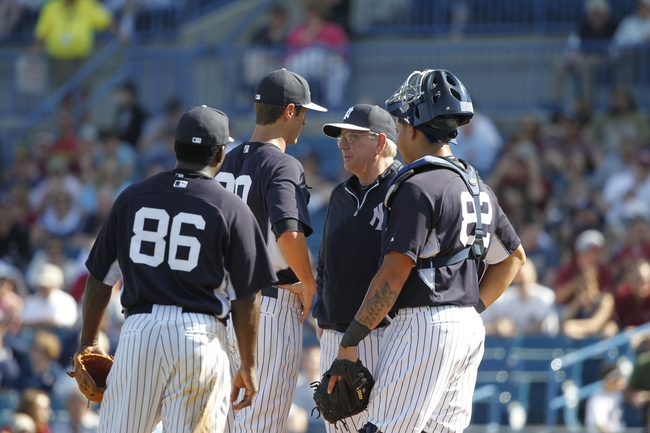 Feb 25, 2014; Tampa, FL, USA; New York Yankees pitching coach Larry Rothschild (58) comes out to talk with pitcher Shane Greene (90) on the mound during the sixth inning agaiinst the Florida State Seminoles at George M. Steinbrenner Field. Mandatory Credit: Kim Klement-USA TODAY Sports