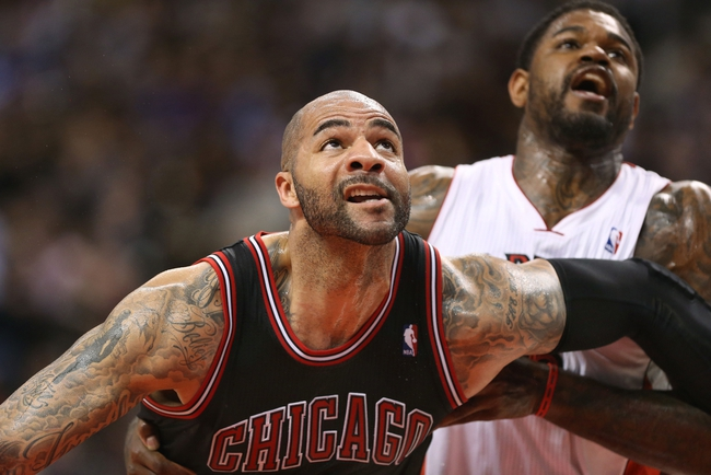 Feb 19, 2014; Toronto, Ontario, CAN; Chicago Bulls forward Carlos Boozer (5) tries to box out Toronto Raptors forward Amir Johnson (15) as they battle for a rebound at Air Canada Centre. The Bulls beat the Raptors 94-92. Mandatory Credit: Tom Szczerbowski-USA TODAY Sports