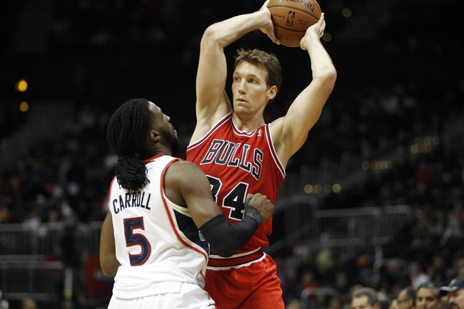 Feb 25, 2014; Atlanta, GA, USA; Chicago Bulls small forward Mike Dunleavy (34) is defended by Atlanta Hawks small forward DeMarre Carroll (5) in the first quarter at Philips Arena. Mandatory Credit: Brett Davis-USA TODAY Sports