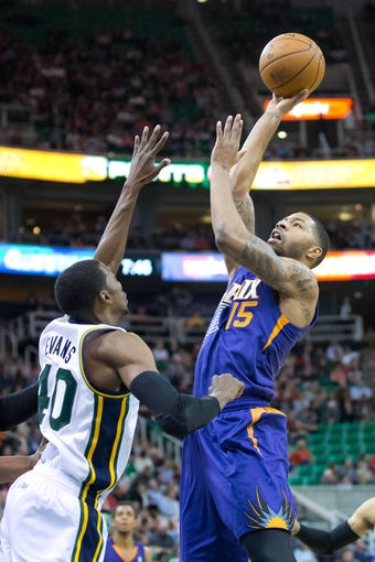 Feb 26, 2014; Salt Lake City, UT, USA; Phoenix Suns power forward Marcus Morris (15) shoots over Utah Jazz small forward Jeremy Evans (40) during the first half at EnergySolutions Arena. Mandatory Credit: Russ Isabella-USA TODAY Sports