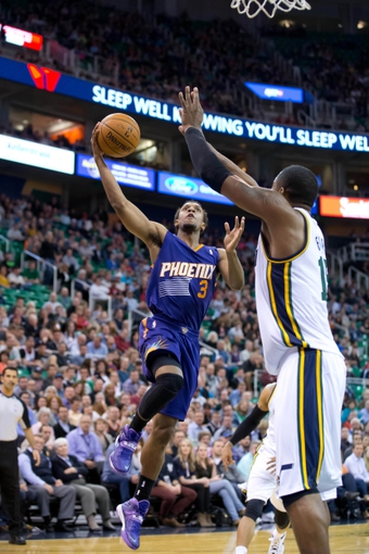 Feb 26, 2014; Salt Lake City, UT, USA; Phoenix Suns point guard Ish Smith (3) goes to the basket against Utah Jazz center Derrick Favors (15) during the first half at EnergySolutions Arena. Mandatory Credit: Russ Isabella-USA TODAY Sports