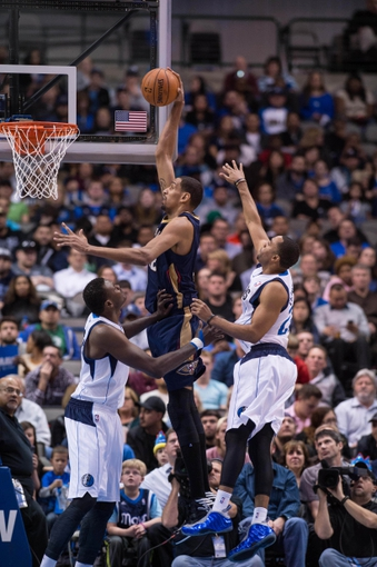 Feb 26, 2014; Dallas, TX, USA; New Orleans Pelicans center Alexis Ajinca (42) dunks over Dallas Mavericks center Samuel Dalembert (1) during the second half at the American Airlines Center. The Mavericks defeated the Pelicans 108-89. Mandatory Credit: Jerome Miron-USA TODAY Sports
