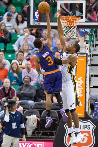 Feb 26, 2014; Salt Lake City, UT, USA; Phoenix Suns point guard Ish Smith (3) shoots against Utah Jazz center Derrick Favors (15) during the second half at EnergySolutions Arena. The Jazz won 109-86. Mandatory Credit: Russ Isabella-USA TODAY Sports