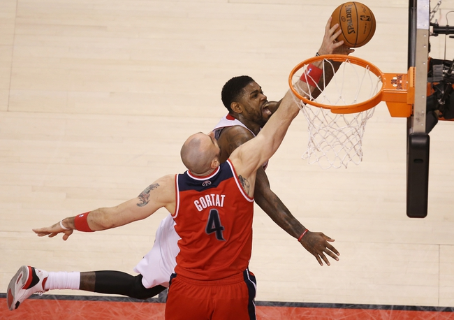 Feb 27, 2014; Toronto, Ontario, CAN; Toronto Raptors forward Amir Johnson (15) goes to the basket against Washington Wizards center Marcin Gortat (4) at Air Canada Centre. Mandatory Credit: Tom Szczerbowski-USA TODAY Sports