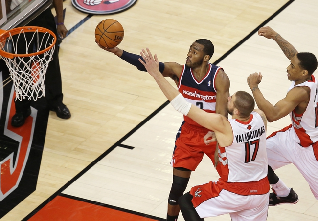 Feb 27, 2014; Toronto, Ontario, CAN; Washington Wizards guard John Wall (10) ties the game by scoring on a lay-up late in the first overtime period against the Toronto Raptors at Air Canada Centre. Mandatory Credit: Tom Szczerbowski-USA TODAY Sports