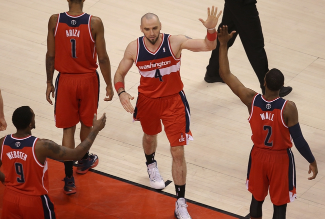 Feb 27, 2014; Toronto, Ontario, CAN; Washington Wizards center Marcin Gortat (4) is congratulated by guard John Wall (10) and forward Martell Webster (9) after scoring a basket in triple overtime against the Toronto Raptors at Air Canada Centre. The Wizards beat the Raptors 134-129 in triple overtime. Mandatory Credit: Tom Szczerbowski-USA TODAY Sports