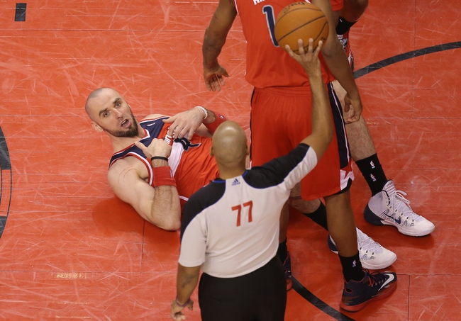 Feb 27, 2014; Toronto, Ontario, CAN; Washington Wizards center Marcin Gortat (4) argues after he was called for his sixth foul of the game by official Karl Lane (77) against the Toronto Raptors at Air Canada Centre. The Wizards beat the Raptors 134-129 in triple overtime. Mandatory Credit: Tom Szczerbowski-USA TODAY Sports