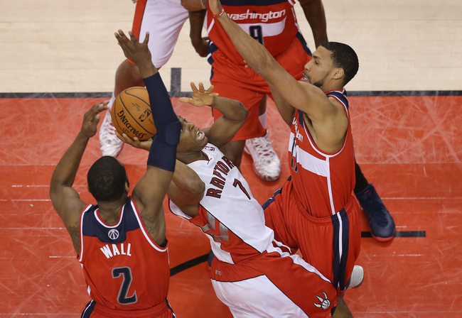 Feb 27, 2014; Toronto, Ontario, CAN; Toronto Raptors point guard Kyle Lowry (7) tries to win the game on the last play of the first overtime period but cannot convert against Washington Wizards guard John Wall (2) at Air Canada Centre. The Wizards beat the Raptors 134-129 in triple overtime. Mandatory Credit: Tom Szczerbowski-USA TODAY Sports