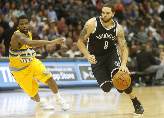 Feb 27, 2014; Denver, CO, USA; Brooklyn Nets guard Deron Williams (8) drives to the basket past Denver Nuggets guard Aaron Brooks (0) during the second half at Pepsi Center.  The Nets won 112-89.  Mandatory Credit: Chris Humphreys-USA TODAY Sports