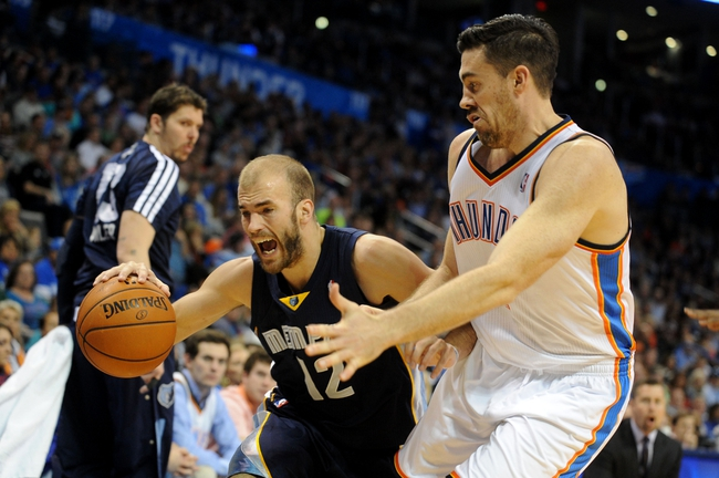 Feb 28, 2014; Oklahoma City, OK, USA; Memphis Grizzlies shooting guard Nick Calathes (12) handles the ball against Oklahoma City Thunder power forward Nick Collison (4) during the second quarter at Chesapeake Energy Arena. Mandatory Credit: Mark D. Smith-USA TODAY Sports
