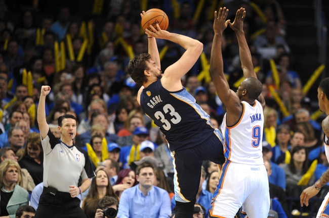 Feb 28, 2014; Oklahoma City, OK, USA; Memphis Grizzlies center Marc Gasol (33) attempts a shot against Oklahoma City Thunder power forward Serge Ibaka (9) while NBA official Pat Fraher looks on during the third quarter at Chesapeake Energy Arena. Mandatory Credit: Mark D. Smith-USA TODAY Sports