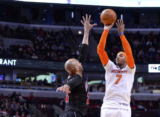 Mar 2, 2014; Chicago, IL, USA; New York Knicks small forward Carmelo Anthony (7) shoots a three point basket against Chicago Bulls power forward Taj Gibson (22) during the first half at the United Center. Mandatory Credit: Mike DiNovo-USA TODAY Sports