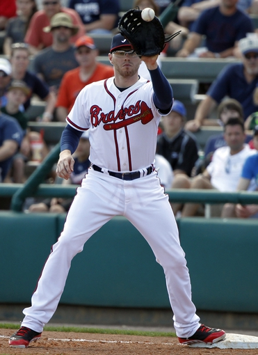 Mar 2, 2014; Lake Buena Vista, FL, USA; Atlanta Braves first baseman Freddie Freeman (5) catches the ball at first for an out during the sixth inning against the Detroit Tigers at Champion Stadium. Mandatory Credit: Kim Klement-USA TODAY Sports