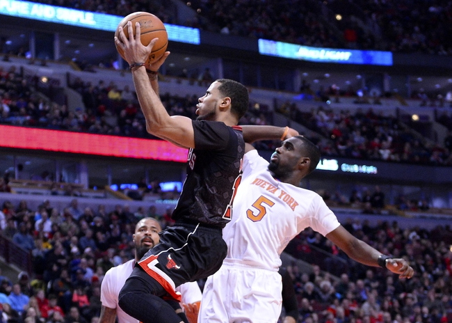 Mar 2, 2014; Chicago, IL, USA; Chicago Bulls point guard D.J. Augustin (14) shoots the ball against New York Knicks shooting guard Tim Hardaway Jr. (5) during the second half at the United Center. Chicago defeats New York 109-90. Mandatory Credit: Mike DiNovo-USA TODAY Sports