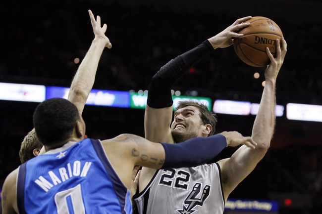 Mar 2, 2014; San Antonio, TX, USA; San Antonio Spurs forward Tiago Splitter (right) shoots while being defended by Dallas Mavericks forward Dirk Nowitzki (left) and Shawn Marion (front) during the first half at AT&T Center. Mandatory Credit: Soobum Im-USA TODAY Sports