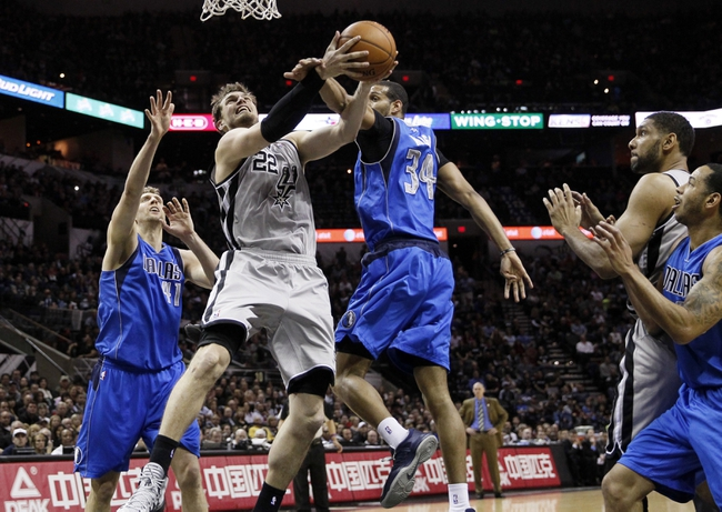 Mar 2, 2014; San Antonio, TX, USA; San Antonio Spurs forward Tiago Splitter (22) drives for the basket between Dallas Mavericks forward Brandan Wright (34) and Dirk Nowitzki (41) during the first half at AT&T Center. Mandatory Credit: Soobum Im-USA TODAY Sports