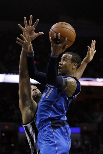 Mar 2, 2014; San Antonio, TX, USA; Dallas Mavericks guard Monta Ellis (right) shoots while being defended by San Antonio Spurs forward Tim Duncan (left) during the second half at AT&T Center. Mandatory Credit: Soobum Im-USA TODAY Sports