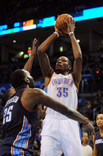Mar 2, 2014; Oklahoma City, OK, USA; Oklahoma City Thunder small forward Kevin Durant (35) attempts a shot against Charlotte Bobcats center Al Jefferson (25) during the third quarter at Chesapeake Energy Arena. Mandatory Credit: Mark D. Smith-USA TODAY Sports