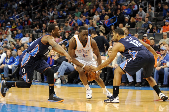 Mar 2, 2014; Oklahoma City, OK, USA; Oklahoma City Thunder point guard Reggie Jackson (15) handles the ball against Charlotte Bobcats point guard Kemba Walker (15) and shooting guard Gary Neal (12) during the fourth quarter at Chesapeake Energy Arena. Mandatory Credit: Mark D. Smith-USA TODAY Sports