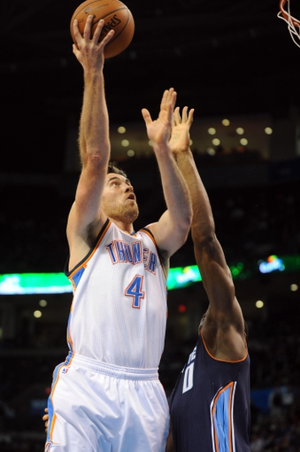 Mar 2, 2014; Oklahoma City, OK, USA; Oklahoma City Thunder power forward Nick Collison (4) attempts a shot against Charlotte Bobcats center Bismack Biyombo (0) during the third quarter at Chesapeake Energy Arena. Mandatory Credit: Mark D. Smith-USA TODAY Sports