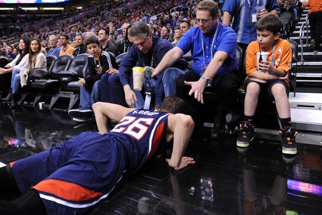 Mar 2, 2014; Phoenix, AZ, USA; Atlanta Hawks shooting guard Kyle Korver (26) falls near Phoenix Suns fans during the second half at US Airways Center. The Phoenix Suns won the game 129-120. Mandatory Credit: Joe Camporeale-USA TODAY Sports