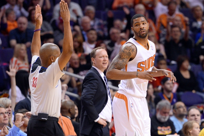 Mar 2, 2014; Phoenix, AZ, USA;  Atlanta Hawks head coach Mike Budenholzer looks on as Phoenix Suns power forward Marcus Morris (15) reacts after making a three point basket during the second half at US Airways Center. The Phoenix Suns won the game 129-120. Mandatory Credit: Joe Camporeale-USA TODAY Sports