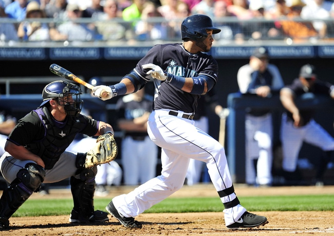 March 3, 2014; Peoria, AZ, USA; Seattle Mariners second baseman Robinson Cano (22) hits a single in the first inning against the Colorado Rockies at Peoria Sports Complex. Mandatory Credit: Gary A. Vasquez-USA TODAY Sports