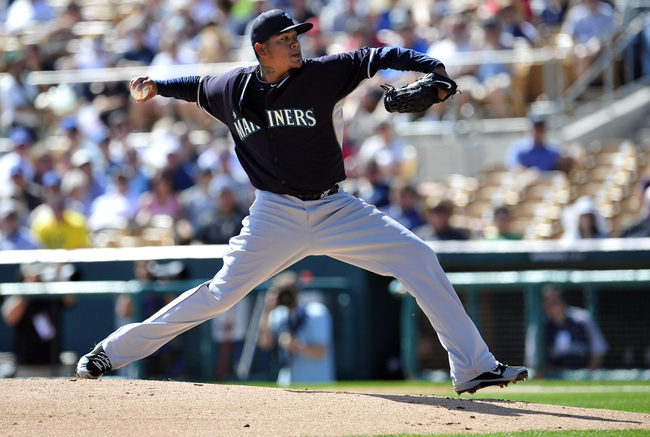 March 4, 2014; Phoenix, AZ, USA; Seattle Mariners starting pitcher Felix Hernandez (34) pitches in the first inning against the Los Angeles Dodgers at Camelback Ranch. Mandatory Credit: Gary A. Vasquez-USA TODAY Sports
