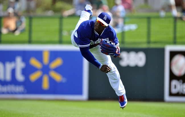 March 4, 2014; Phoenix, AZ, USA; Los Angeles Dodgers right fielder Yasiel Puig (66) throws to the infield to complete an out in the third inning against the Seattle Mariners at Camelback Ranch. Mandatory Credit: Gary A. Vasquez-USA TODAY Sports