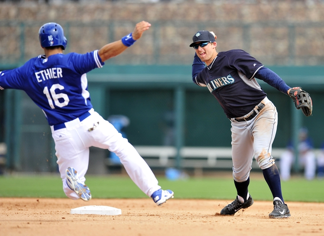 March 4, 2014; Phoenix, AZ, USA; Seattle Mariners shortstop Brad Miller (5) throws to first to complete a double play in the fourth inning as Los Angeles Dodgers center fielder Andre Ethier (16) slides into second at Camelback Ranch. Mandatory Credit: Gary A. Vasquez-USA TODAY Sports