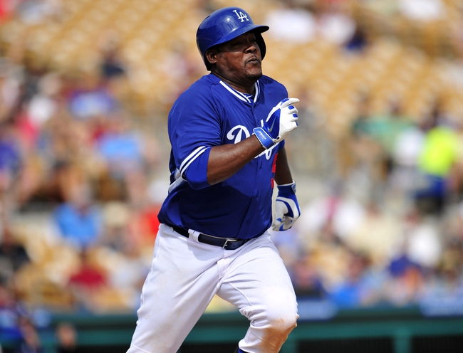 March 4, 2014; Phoenix, AZ, USA; Los Angeles Dodgers third baseman Juan Uribe (5) runs to first after hitting in the fourth inning against the Seattle Mariners at Camelback Ranch. Mandatory Credit: Gary A. Vasquez-USA TODAY Sports
