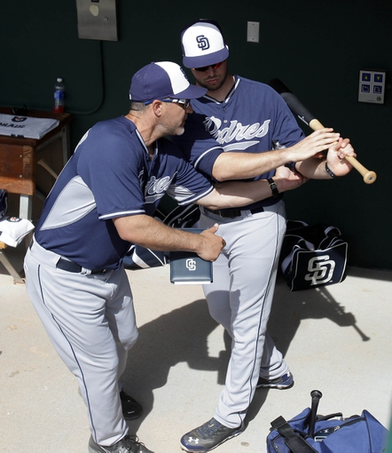 Mar 5, 2014; Phoenix, AZ, USA; San Diego Padres hitting coach Phil Plantier (28) helps Austin Hedges (70) with hitting before a game against the Chicago White Sox at Camelback Ranch. Mandatory Credit: Rick Scuteri-USA TODAY Sports