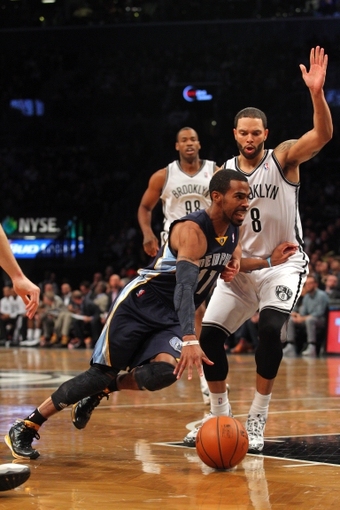 Mar 5, 2014; Brooklyn, NY, USA; Memphis Grizzlies point guard Mike Conley (11) drives around Brooklyn Nets point guard Deron Williams (8) during the second quarter of a game at Barclays Center. Mandatory Credit: Brad Penner-USA TODAY Sports