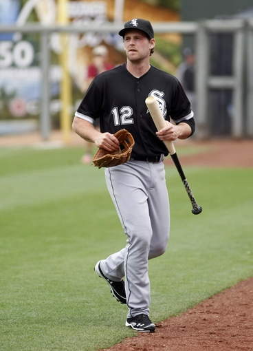 Mar 6, 2014; Surprise, AZ, USA; Chicago White Sox third baseman Conor Gillaspie (12) warms up before a game against the Kansas City Royals at Surprise Stadium. Mandatory Credit: Rick Scuteri-USA TODAY Sports
