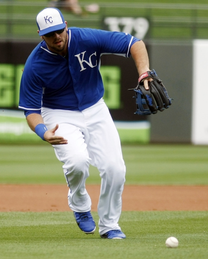 Mar 6, 2014; Surprise, AZ, USA; Kansas City Royals third baseman Mike Moustakas (8) tries to bare hand a ground ball in the first inning against the Chicago White Sox at Surprise Stadium. Mandatory Credit: Rick Scuteri-USA TODAY Sports